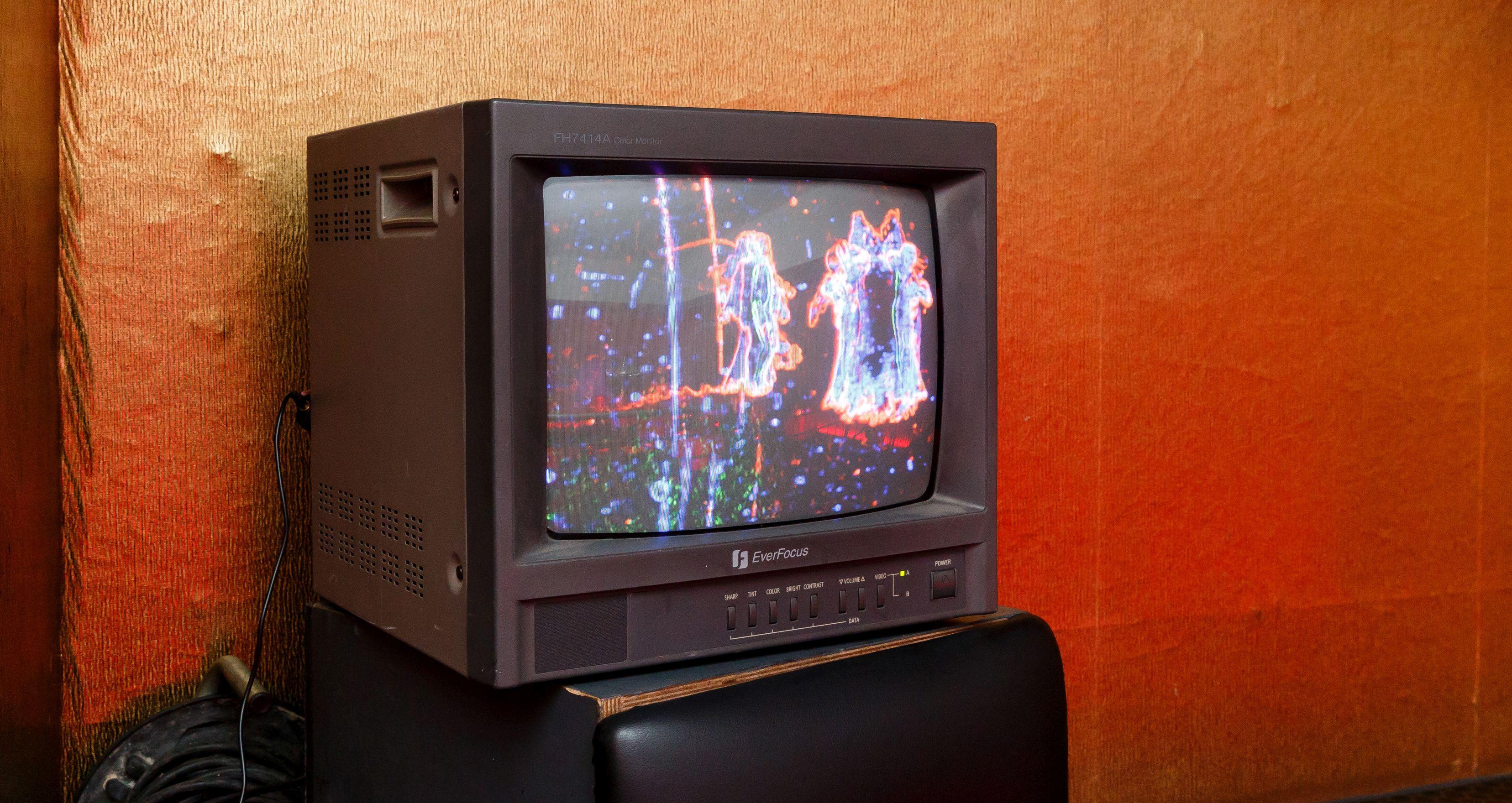 Vor einer goldenen Tapete steht ein alter Röhren-Fernseher. Auf dem Bildschirm sind bunte Strichzeichnungen zu erkennen.