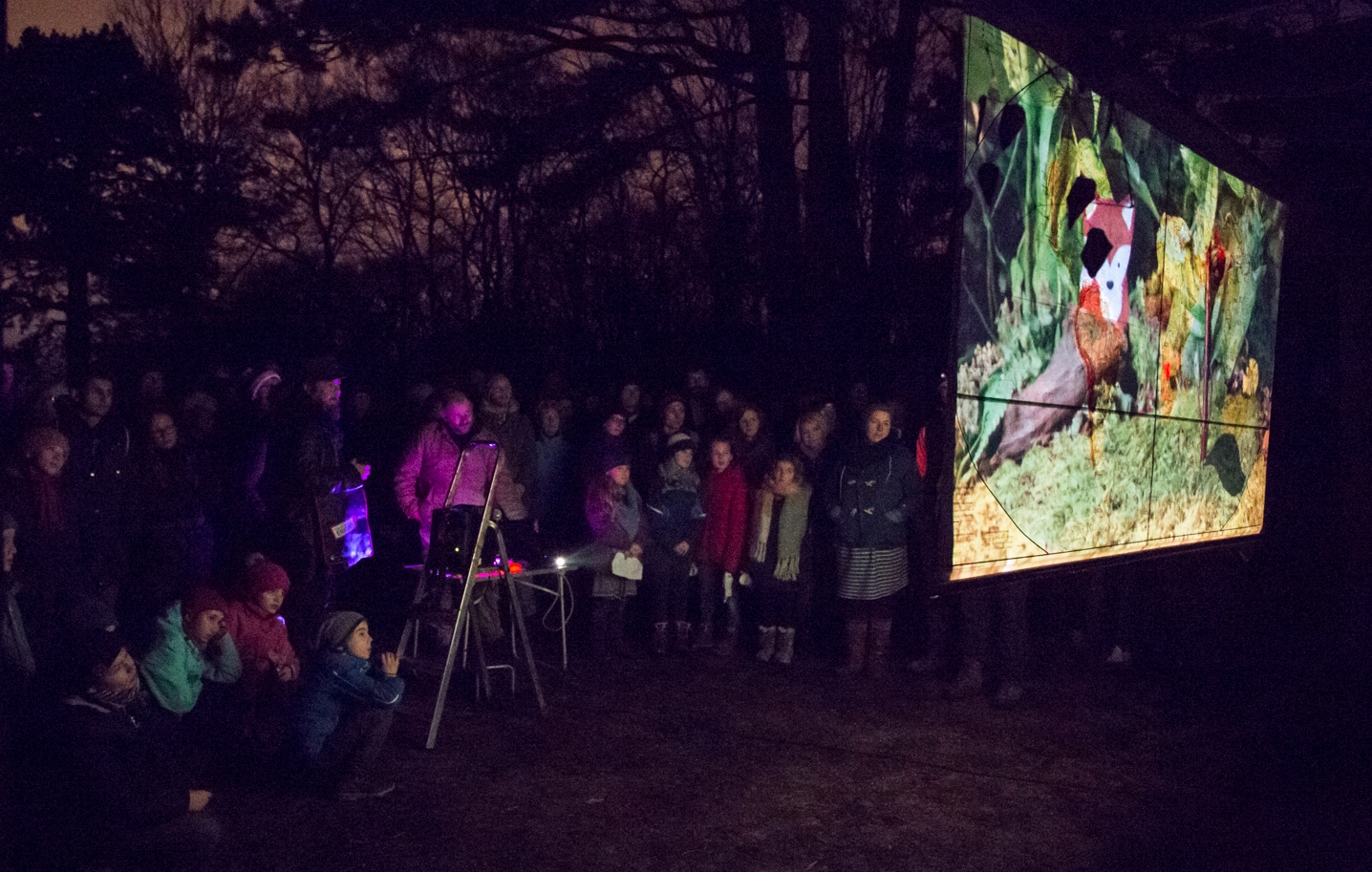 Photo taken during a screening in Erfurt. A group of adults and children watch a film on a screen in the forest.