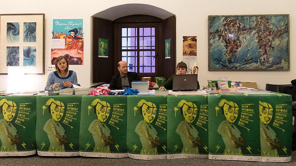 Drei Personen sitzen an einem langen Tresen und arbeiten. Der Tresen ist von mit vielen grünen Plakaten verklebt. Hinten an der Wand hängen Kunstwerke.