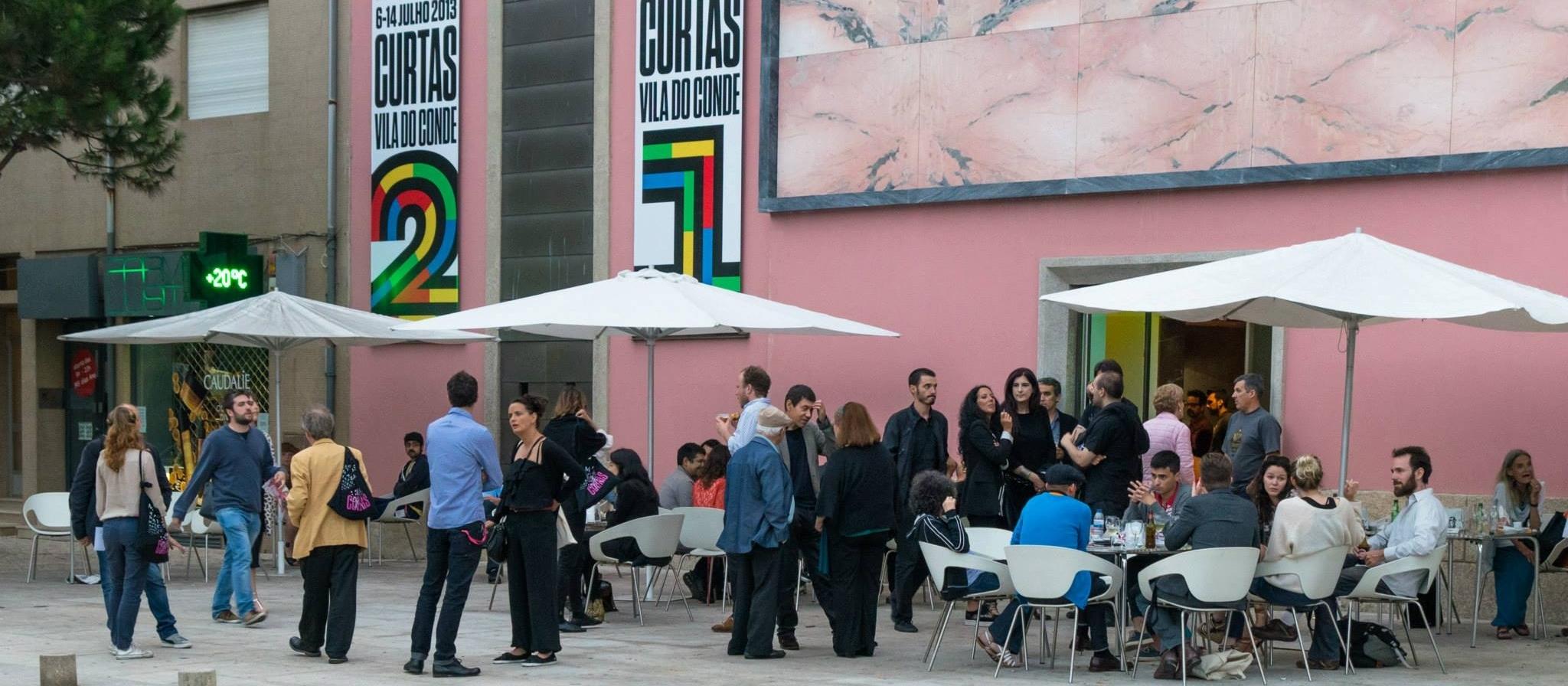 Ein rosafarbenes Gebäude mit großen Bannern. Davor viele Personen in Gruppen. Sie sitzen oder stehen unter großen Sonneschirmen. Viele sind ins Gespräch vertieft.